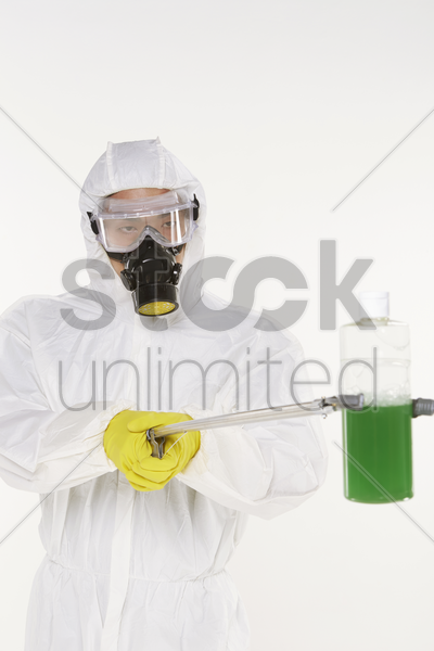 man in protective suit holding up a bottle of chemical stock photo