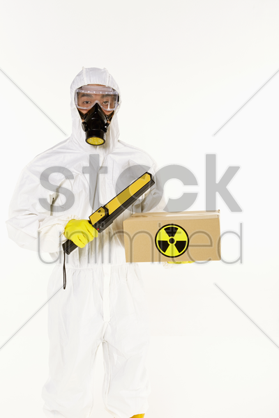 man in protective suit inspecting a radioactive box stock photo