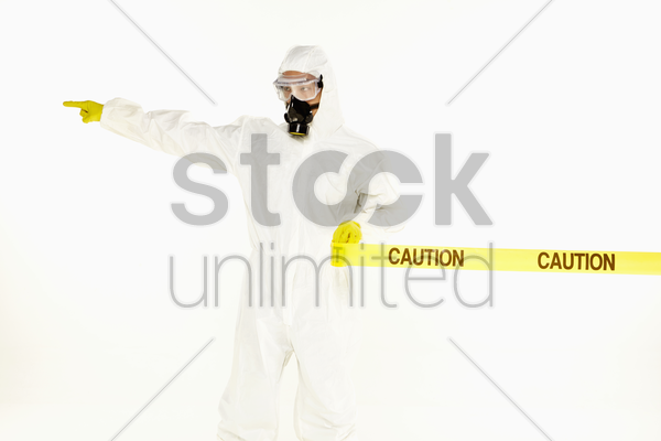 man in protective suit rolling out the 'caution' tape, pointing to the right stock photo