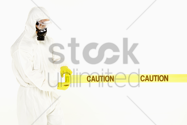 man in protective suit rolling out the 'caution' tape stock photo