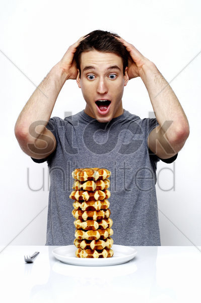 man in shock looking at a stack of doughnuts stock photo