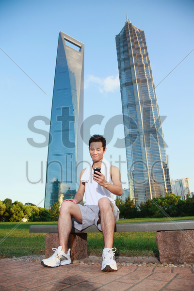 man in sports clothing text messaging on the phone stock photo
