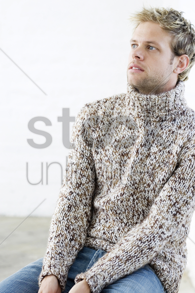 man in sweater thinking stock photo