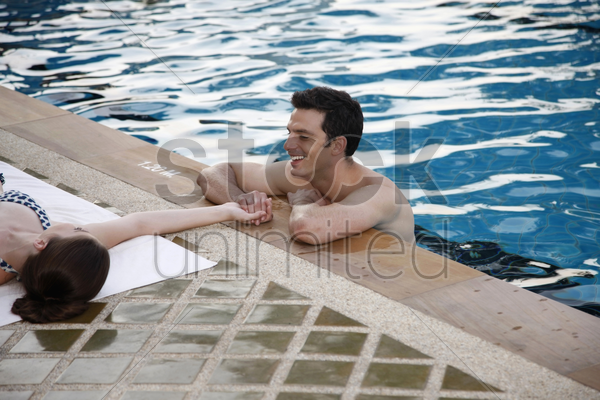 man in swimming pool flirting with woman stock photo