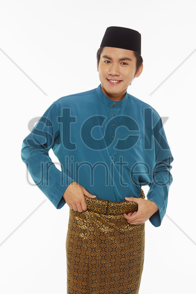 man in traditional clothing adjusting his sarong stock photo