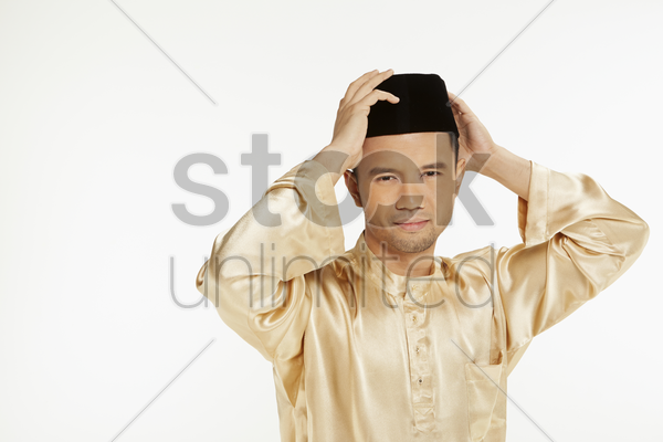 man in traditional clothing adjusting his skull cap stock photo