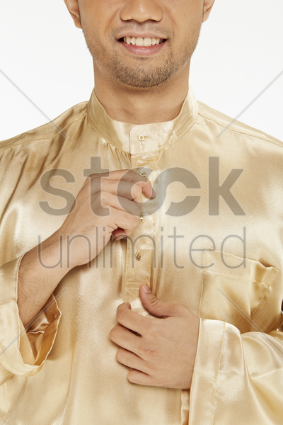 man in traditional clothing buttoning up his blouse stock photo