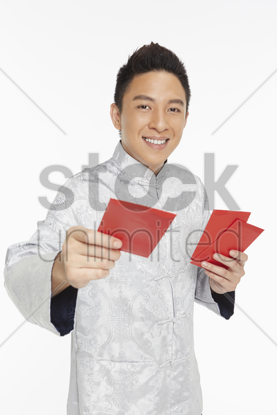 man in traditional clothing handing out red packets stock photo