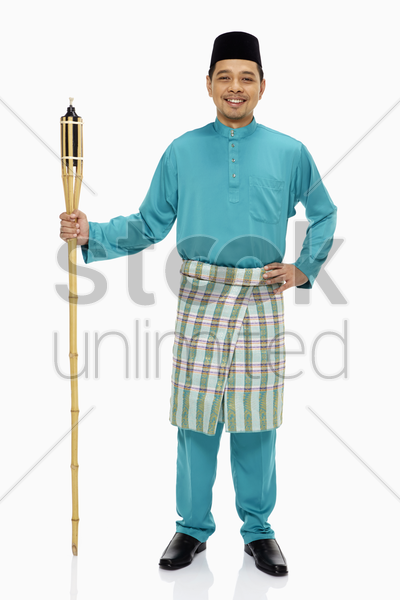 man in traditional clothing holding a bamboo torch stock photo