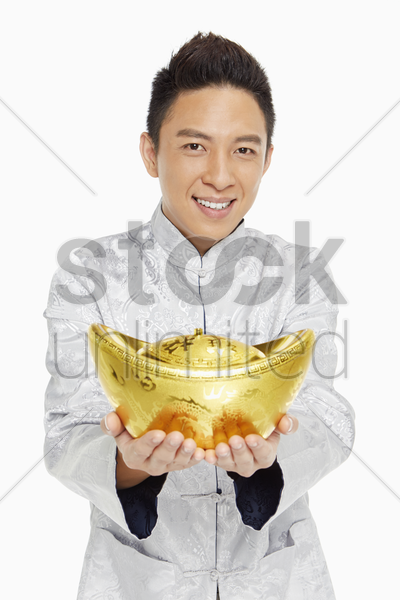man in traditional clothing holding a gold ingot stock photo