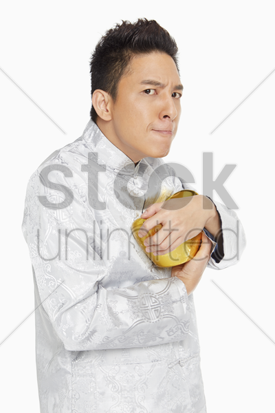 man in traditional clothing holding on tightly to a gold ingot stock photo