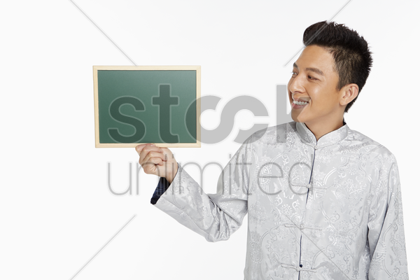 man in traditional clothing holding up a blackboard stock photo
