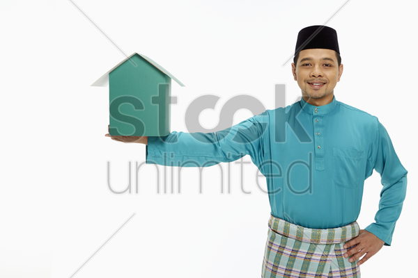 man in traditional clothing holding up a cardboard house stock photo