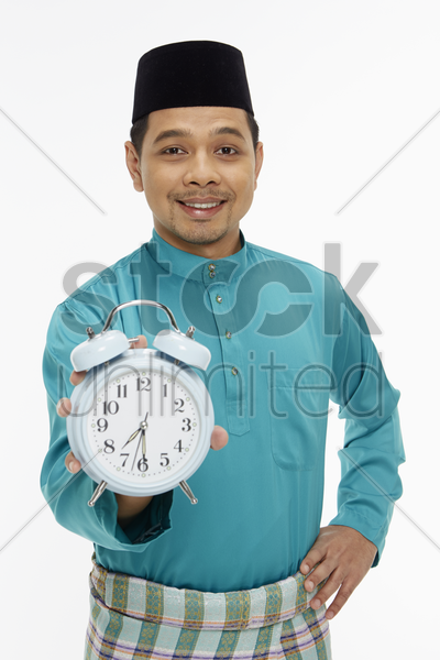 man in traditional clothing holding up a clock stock photo