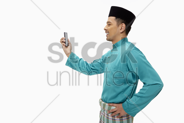 man in traditional clothing holding up a mobile phone stock photo