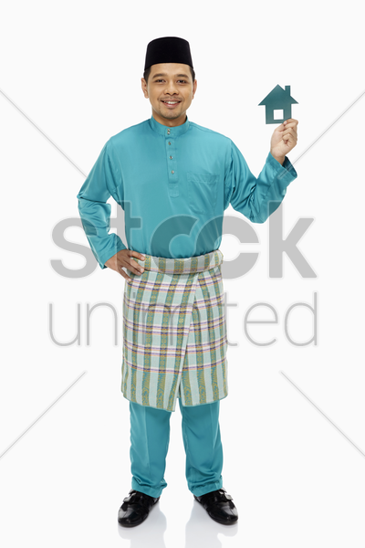 man in traditional clothing holding up a small cardboard house stock photo