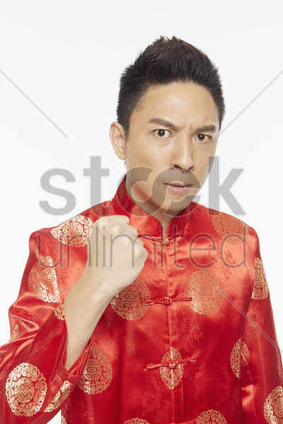 man in traditional clothing holding up his fist stock photo