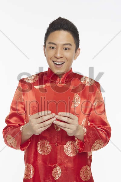 man in traditional clothing holding up red packets stock photo
