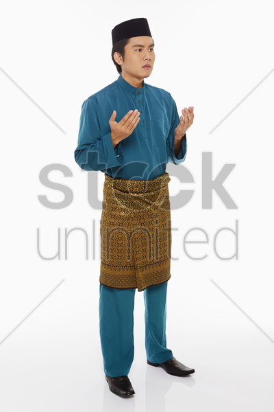 man in traditional clothing lifting up hands, praying stock photo