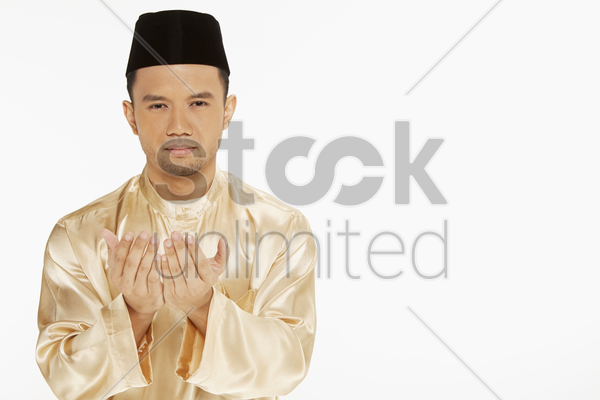 man in traditional clothing lifting up his hands, praying stock photo