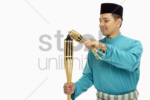 man in traditional clothing lighting up the bamboo torches stock photo