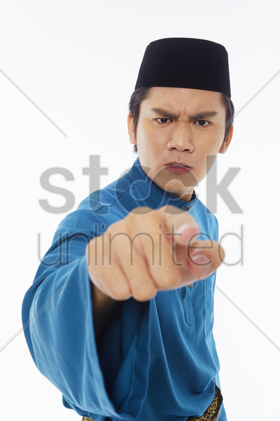 man in traditional clothing looking angry stock photo