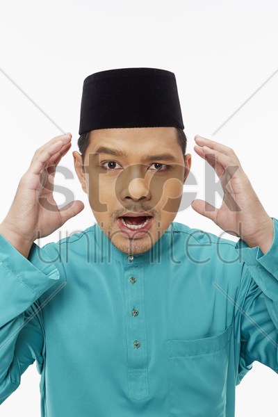 man in traditional clothing looking frustrated stock photo