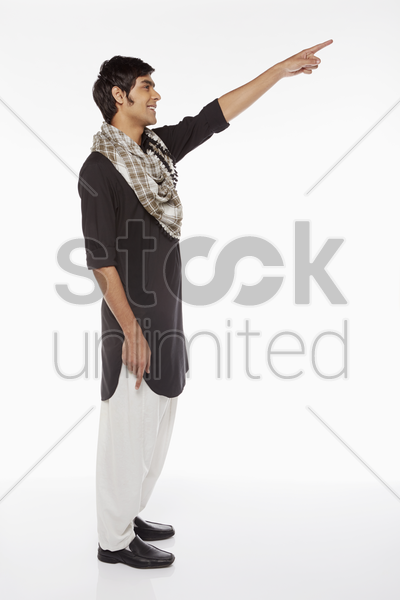 man in traditional clothing pointing towards the left stock photo