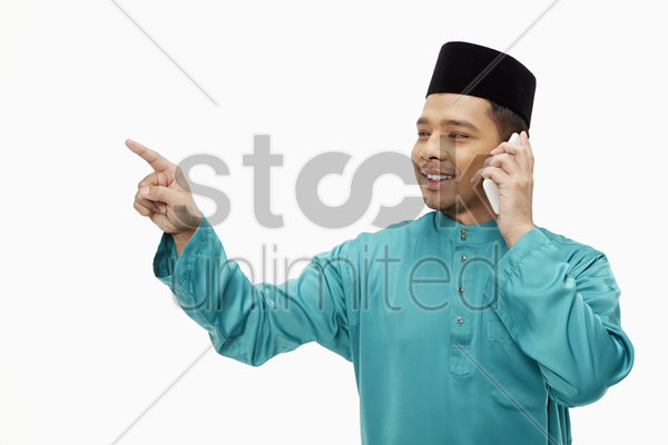 man in traditional clothing pointing while talking on mobile phone stock photo
