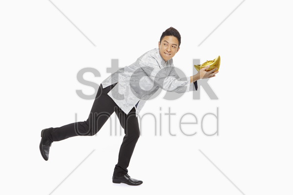 man in traditional clothing posing while holding a gold ingot stock photo