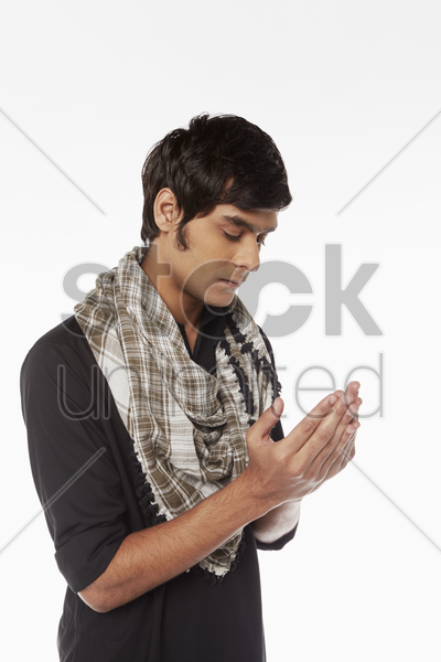 man in traditional clothing praying stock photo