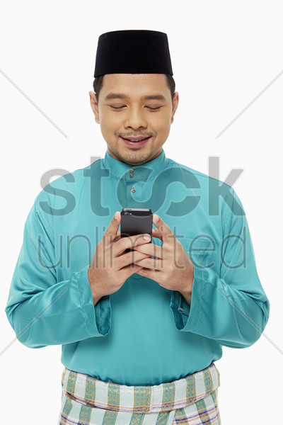 man in traditional clothing sending a text message stock photo