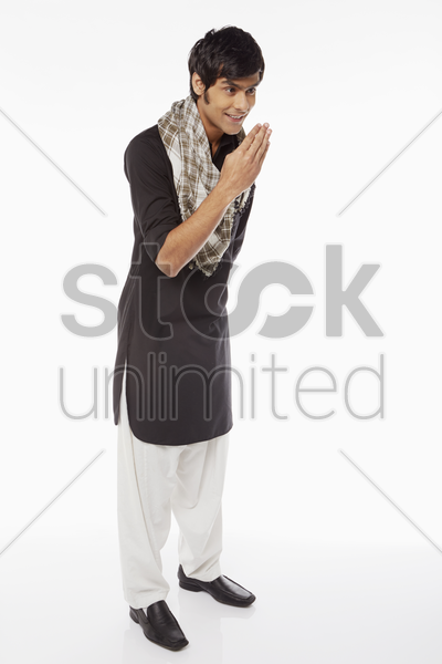 man in traditional clothing showing an islamic greeting gesture stock photo