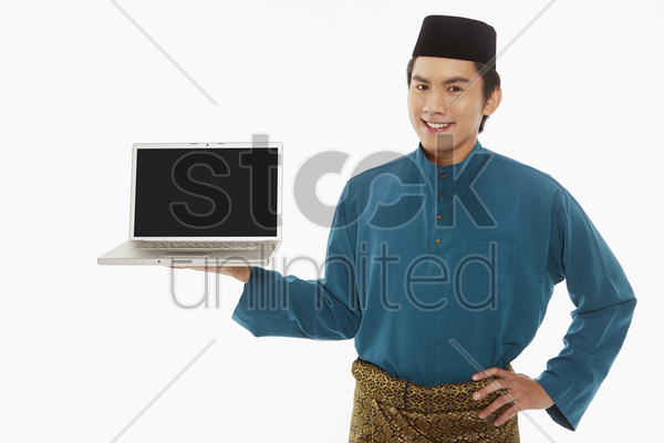 man in traditional clothing showing laptop stock photo