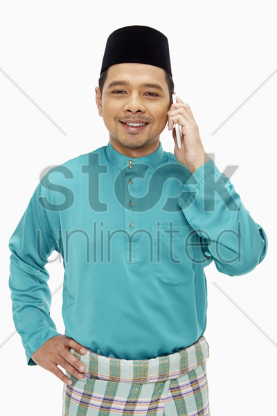 man in traditional clothing talking on mobile phone stock photo