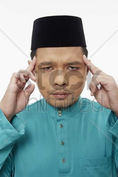 man in traditional clothing touching his forehead stock photo