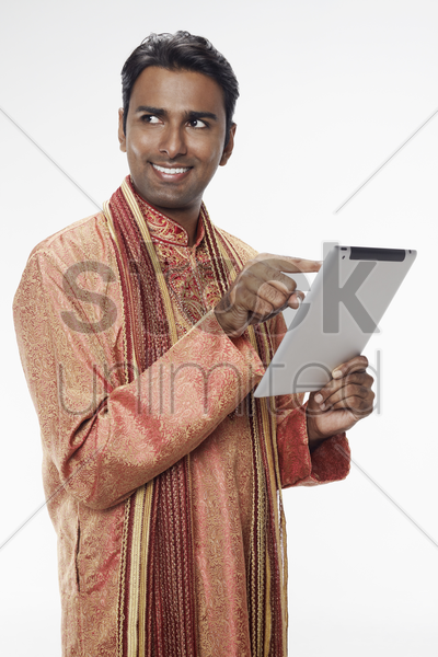 man in traditional clothing using digital tablet stock photo