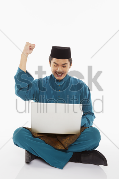 man in traditional clothing using laptop and cheering stock photo