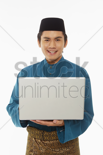 man in traditional clothing using laptop stock photo