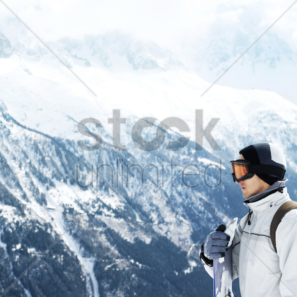 man in warm clothing and ski goggles holding snowboard stock photo