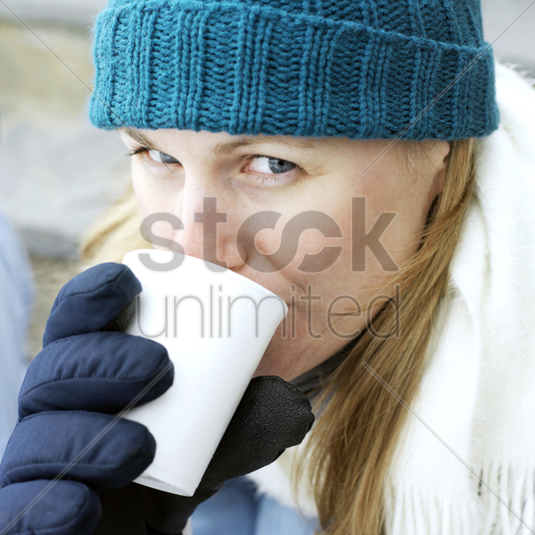 man in warm clothing enjoying a cup of hot drink stock photo