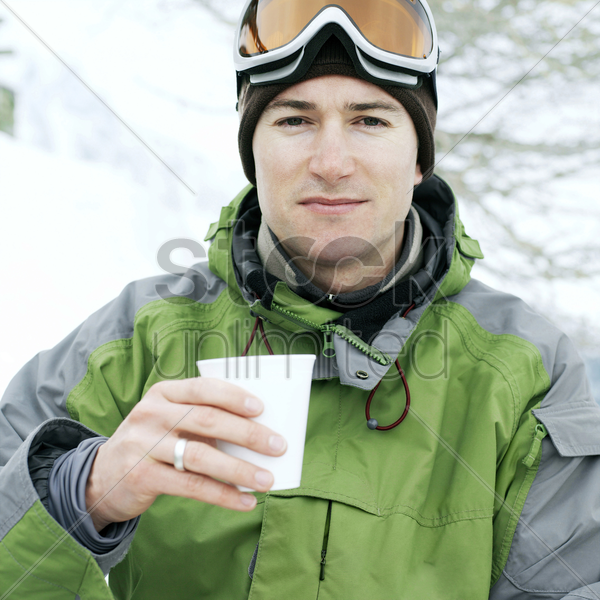 man in warm clothing holding a cup of hot drink stock photo
