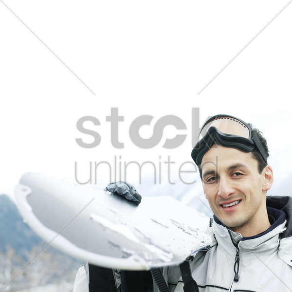 man in warm clothing holding ski board stock photo