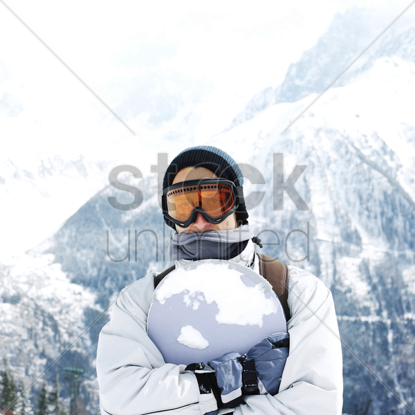 man in warm clothing hugging snowboard stock photo