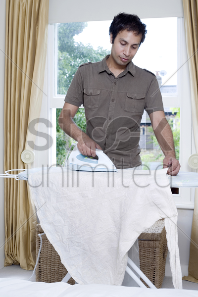 man ironing clothes stock photo