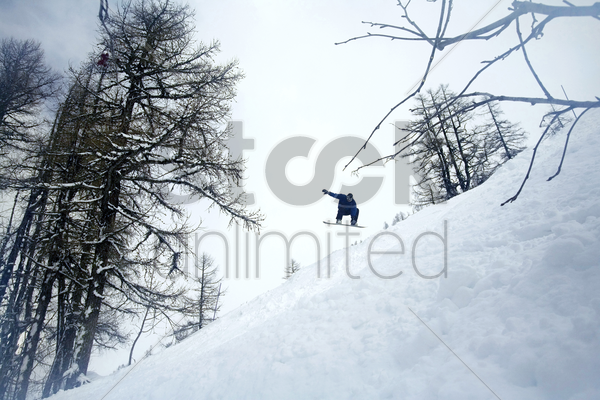 man jumping in mid air on snowboard stock photo