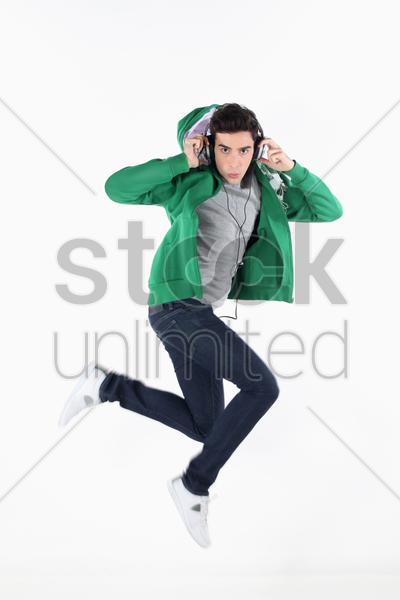 man jumping in the air while listening to music on mp3 player stock photo