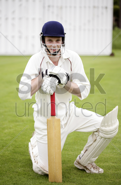 man kneeling down while holding a cricket bat stock photo