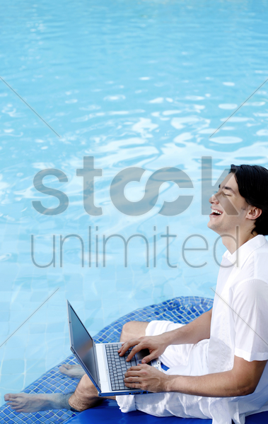 man laughing while using laptop by the pool side stock photo