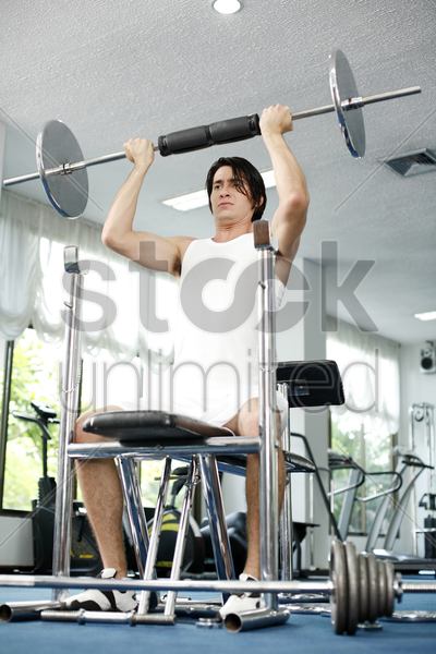 man lifting barbell in the gym stock photo